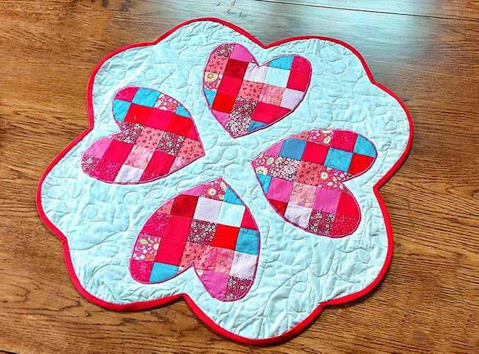 Four multicolored (red, pink, blue, red/pink flowered and patterned) squares cut into hearts are appliqued with pink thread on a white background. You see machine-quilted patterns on the white background. The table topper has scalloped edges and red binding.