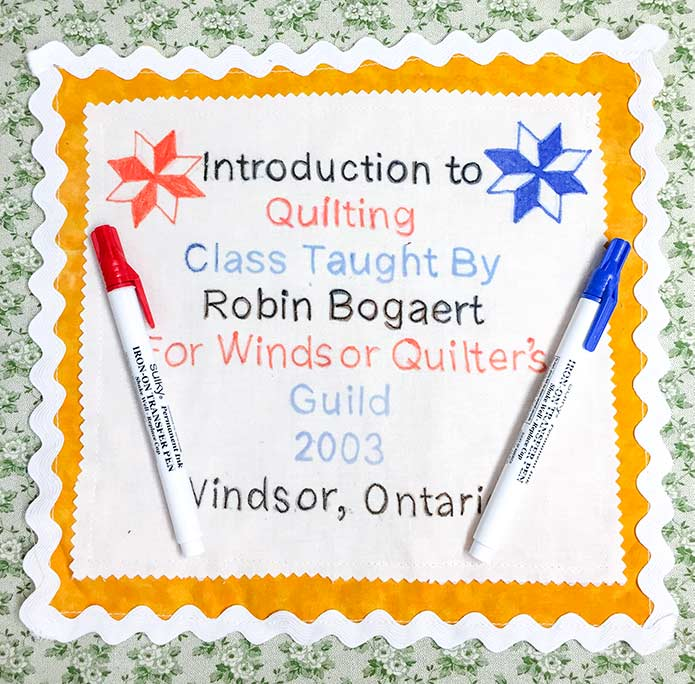 A quilt label made with Sulky Transfer Pens, and two of the pens used for the project.