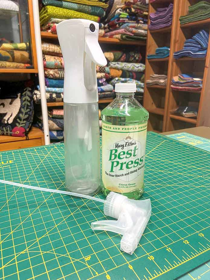"A bottle of Mary Ellen's Citrus Grove Best Press, the detached nozzle and an empty white Best Press Spay and Misting bottle are displayed sitting on a green cutting mat with a shelf of folded quilts in the background. Mary Ellen's Best Press, HeatnBond Lite Iron-On Adhesive Sheets, Olfa 5"" Stainless Steel Serrated Edge Scissors, Heirloom Non-Stick Teflon Applique Mat, Oliso M2Pro Mini Project Iron."