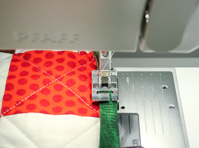 The quilt's binding is held down with the bi-level topstitch presser foot with the needle positioned to the far left ready for sewing