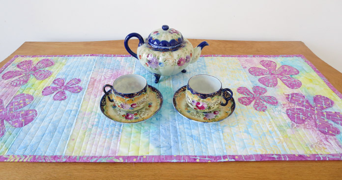 Finished table runner using Banyan Batiks displayed with a teapot and teacups. Brother Innov-ís BQ3050 sewing and quilting machine, MuVit Digital Dual Feed Foot, Sugar Crystals collection by Banyan Batiks