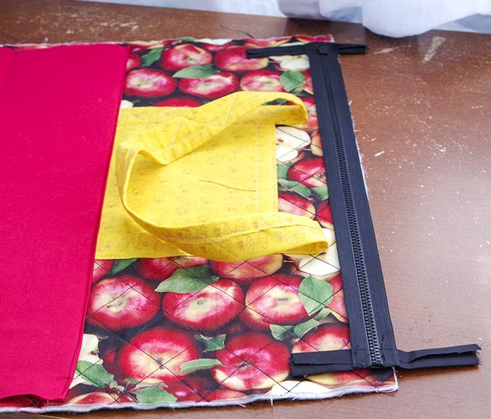 This picture shows the outside of the quilted bag, including one yellow pocket and handle and part of the red bottom of the bag. The black zipper is in place at the top of the bag with the zipper tabs attached, ready to be sewn on.