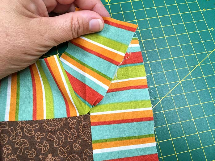 The ends of all four striped borders that were cut with an Olfa rotary cutter, an Omnigrid ruler and a Unique cutting mat are loose.