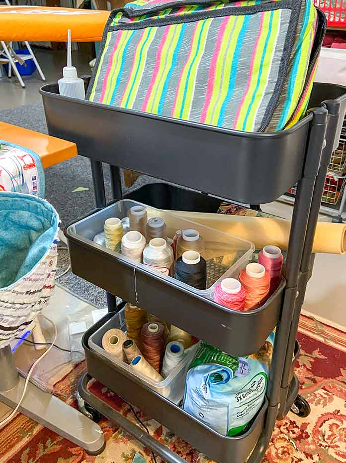 The Vivace Craft & Accessory Tote shown in the top basket of a black rolling 3-tier cart. The other baskets hold cones of thread.