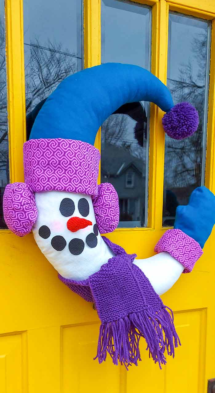 Half-moon shaped white snowman on a yellow door with blue hat and mittens, purple patterned cuff on mitts and hat and purple patterned ear muffs. A dark purple knitted scarf is around the snowman's neck. A crocheted orange carrot nose is surround by glued on leather eyes and mouth. There is a dark purpose pom-pom made out of yarn on the hat.