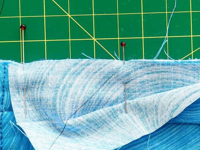 Placing a pin where the diagonal line meets the quilt's edge makes it easier to join both ends of the binding strip. Gütermann threads