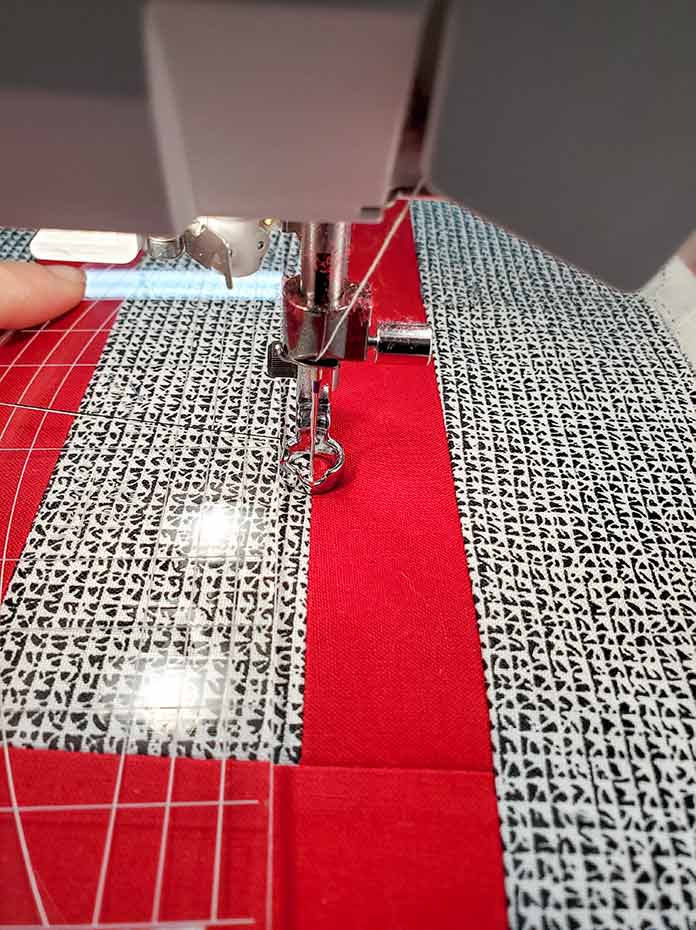 Using a ruler to guide the stitch in the ditch quilting on the Husqvarna Viking Brilliance 75Q