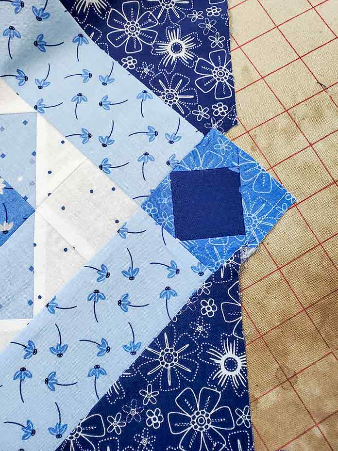 A notch along the side of the quilt when sewing the on-point rows. Spectrum QAL2020 made with the Blue Stitch collection by Riley Blake Designs