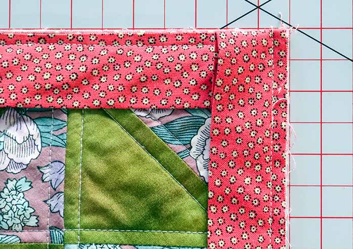 The strip is folded down and sewn along the quilt's next edge