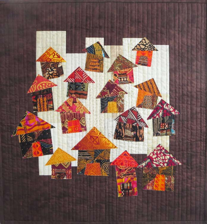 Quilt with applique houses. Brother Innov-ís BQ3050 sewing and quilting machine, MuVit Digital Dual Feed Foot, SA195 MuVit Open-Toe Dual Feed Foot, Mary Ellen's Best Press, Banyan Batiks