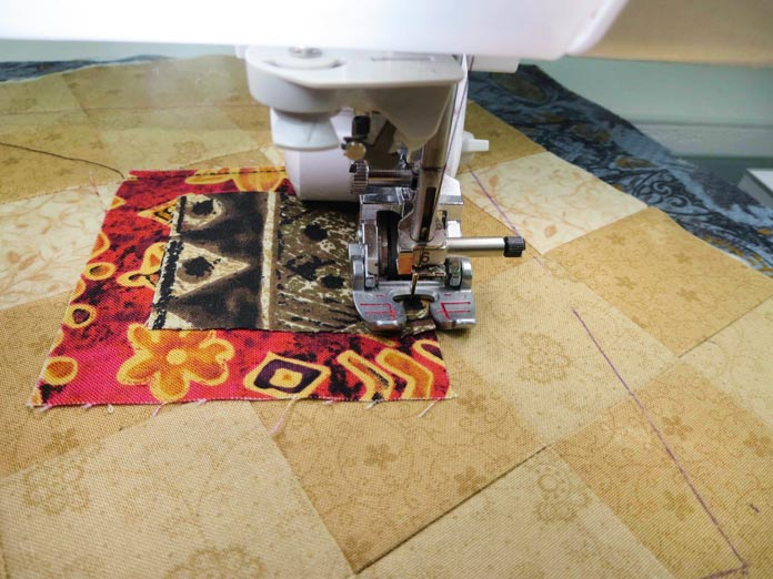 """Stitching the applique pieces to the background using the MuVit digital dual feed foot on a Brother sewing machine. Brother Innov-ís BQ3050 sewing and quilting machine, Mary Ellen's Best Press, Brother SA185 ¼"""" Piecing Foot with Guide, Brother SA125 ¼"""" Quilting Foot, Olfa square ruler, MuVit digital dual feed foot"""