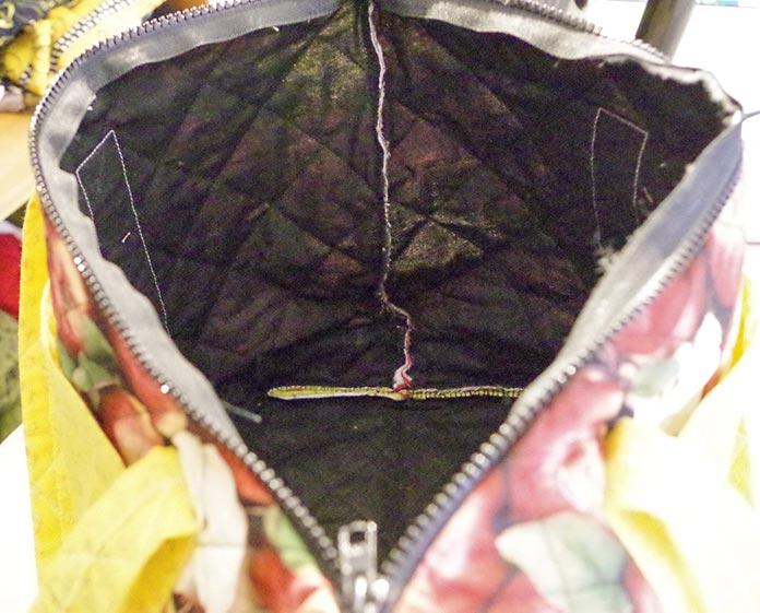 This photo is taken from the end of the bag and shows the inside lining of the apple bag which is black, you can see the side seam and the corner seam for the bottom of the bag. The outside of the bag is visible (the apple fabric and the yellow pockets) and you can see the zipper.