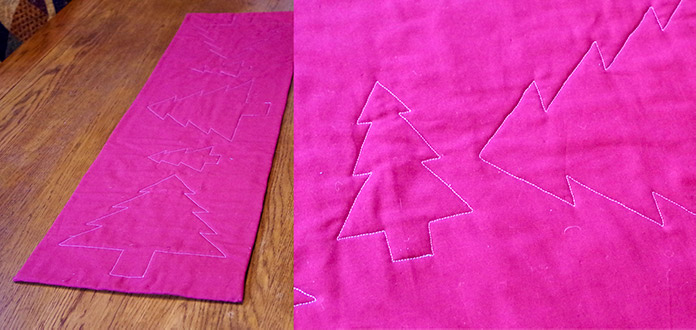 The red back of the quilt is shown with the machine-quilted Christmas trees in white thread on the red background.