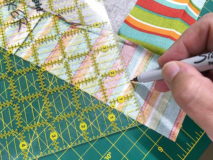 A 45° line is drawn on the back of the striped fabric using an Omnigrid ruler as a guide.