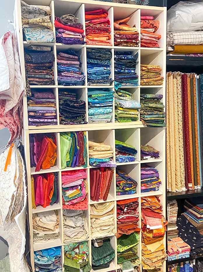 Multicolored fabric pieces are stored in sections of a white storage cabinet. Machine quilting samples hang by two rings on hooks on the left side of the cabinet.