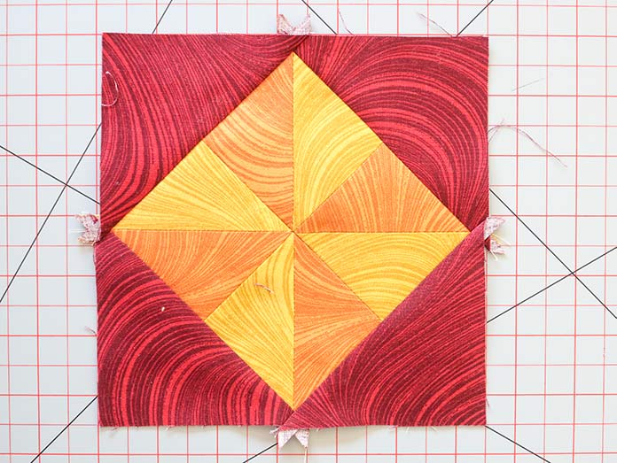 Sew the triangular E fabric pieces to the edges of the block's center.