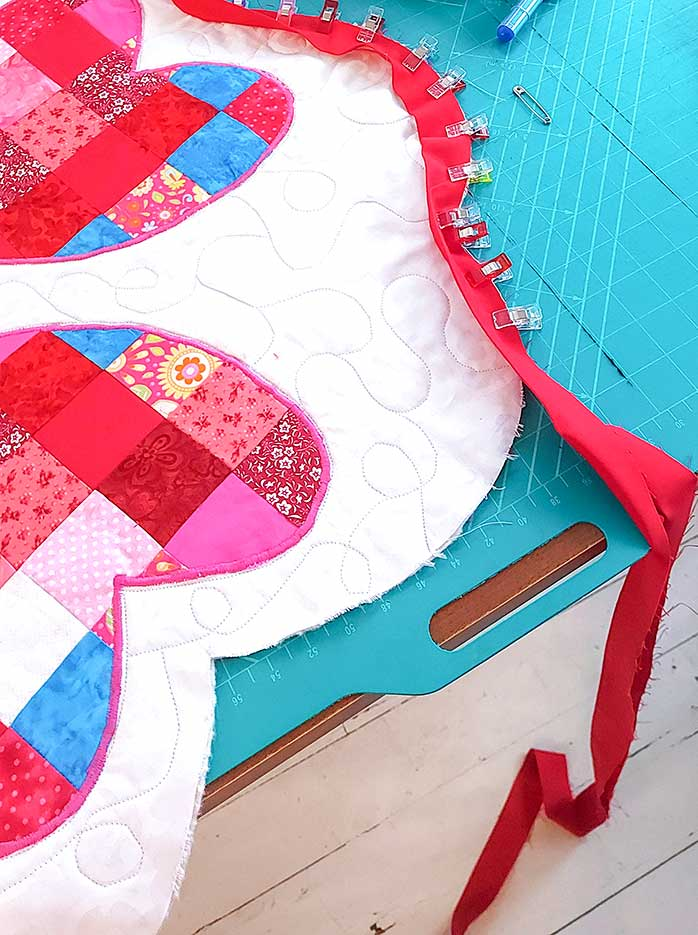 The red binding is clipped on ready to be sewn around the scalloped edge.