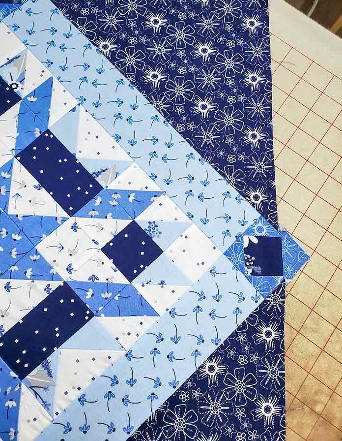 The side of the quilt when sewing the on-point rows. Spectrum QAL2020 made with the Blue Stitch collection by Riley Blake Designs