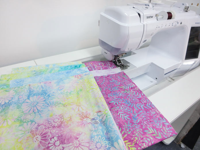Batik fabrics sitting on the bed of a sewing machine Brother Innov-ís BQ3050 sewing and quilting machine, MuVit Digital Dual Feed Foot, SA195 MuVit Open-Toe Dual Feed Foot, Mary Ellen's Best Press, Banyan Batiks