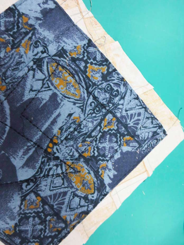 """Fabric is cut 1"""" beyond the line marking the outside edge of the quilt. Brother Innov-ís BQ3050 sewing and quilting machine, Mary Ellen's Best Press, Brother SA185 ¼"""" Piecing Foot with Guide, Brother SA125 ¼"""" Quilting Foot, Olfa square ruler, MuVit digital dual feed foot"""