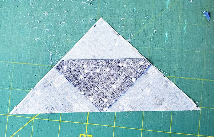 The white triangle is slightly larger than the pieced blue triangle. Block 3 featuring the Blue Stitch collection by Riley Blake Designs.