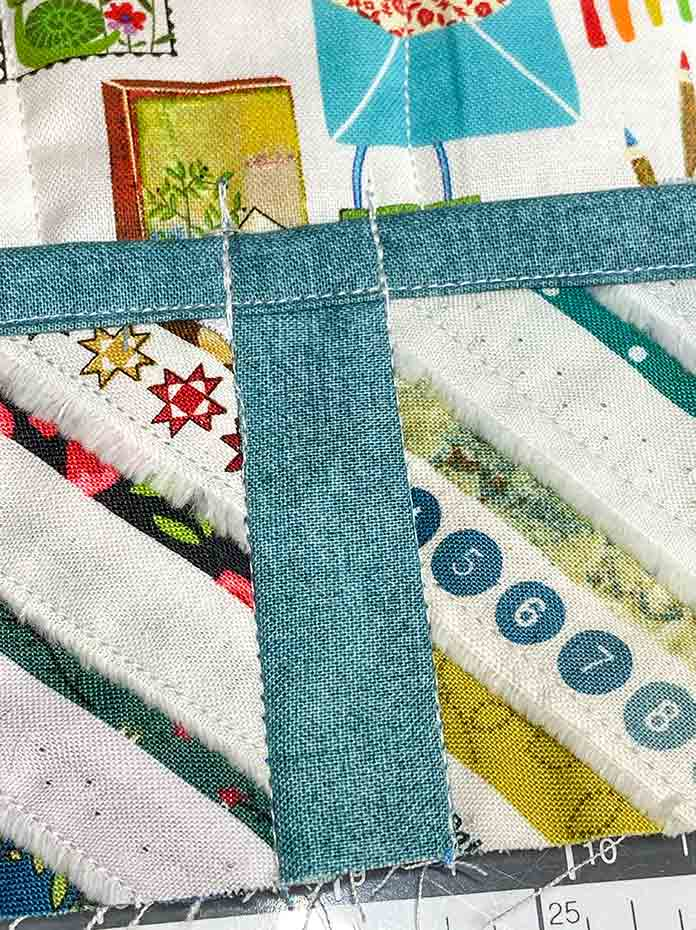 The selvage pocket has been stitched to the sewing machine mat along both sides of the teal accent fabric.
