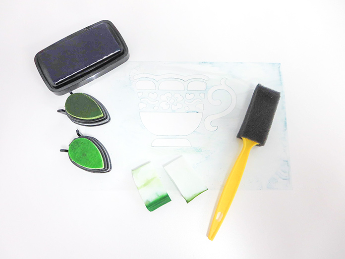 Stenciling supplies: ink, foam pieces, foam brush and stencil, Brother ScanNCut SDX225, 505 temporary fabric adhesive spray, Brother stencil sheet, Brother standard tack cutting mat, Brother spatula and hook set