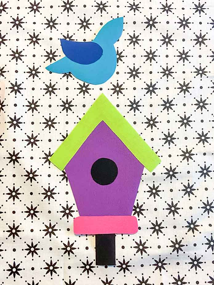 "The birdhouse and the blue bird applique shapes are placed on the black and white background fabric. Mary Ellen's Best Press, HeatnBond Lite Iron-On Adhesive Sheets, Olfa 5"" Stainless Steel Serrated Edge Scissors, Heirloom Non-Stick Teflon Applique Mat, Oliso M2Pro Mini Project Iron."