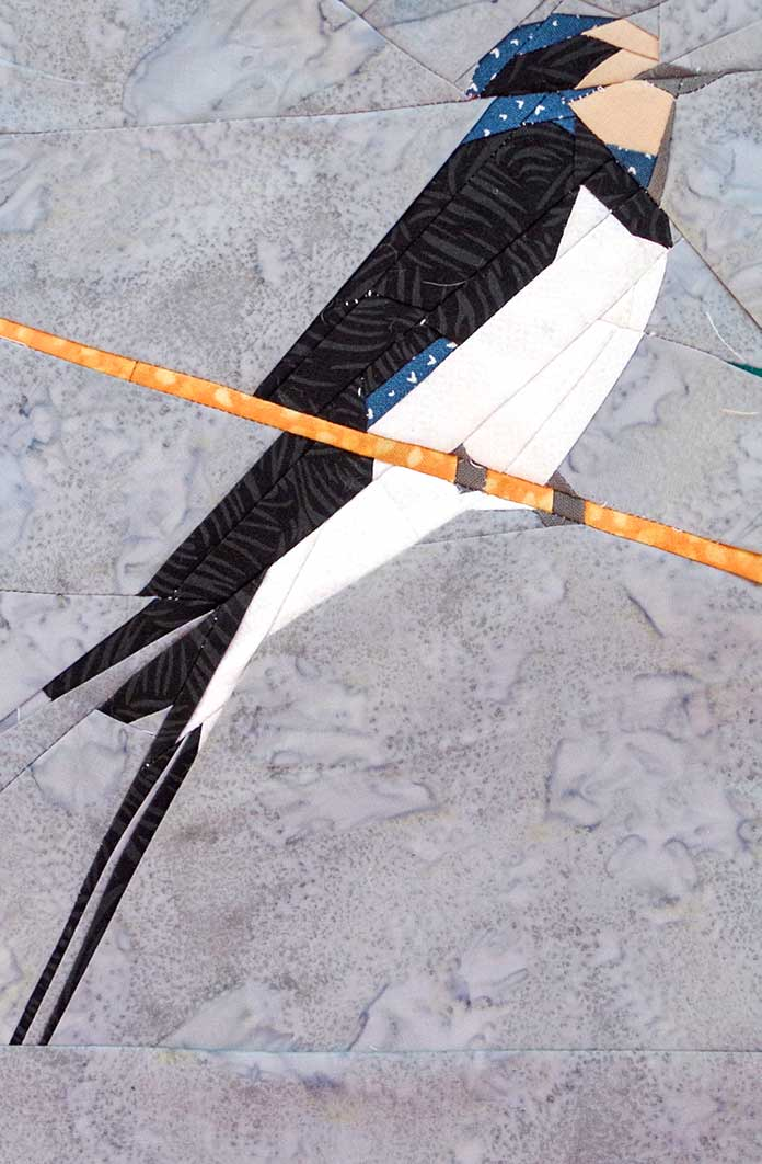 The completed swallow is shown facing the right with long black tail feathers, a white belly, the back and head are a combination of blue and black (mostly black) with a white face dark gray beak. The swallow is sitting on an orange wire, you can see the dark gray feet gripping the wire. The swallow is mounted on light, dappled gray.