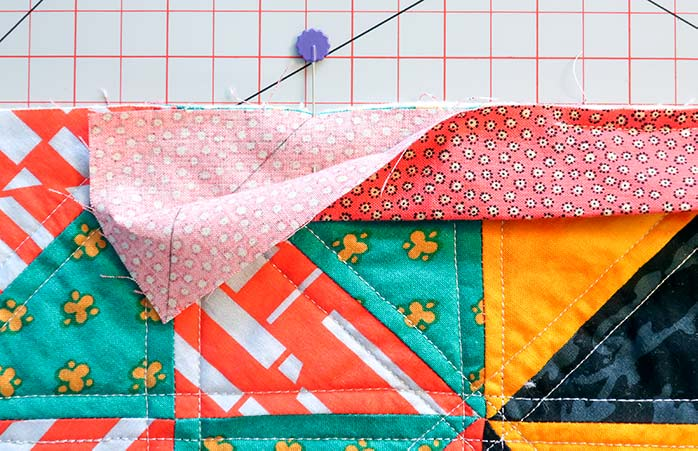 A pin is placed where the diagonal line meets the quilt's edge