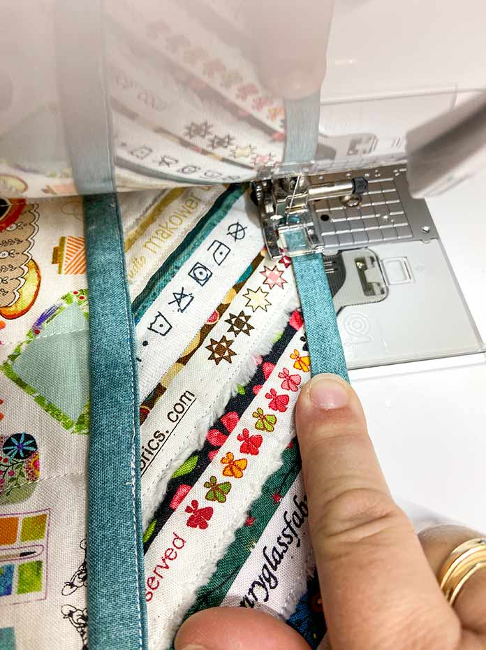 The teal binding is topstitched to the front side of the sewing machine mat.