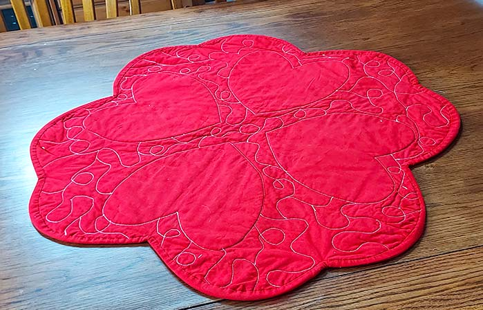 Machine quilting in white thread is shown on the red background of the table topper. Four red hearts are visible as well as the free quilt pattern between each heart.