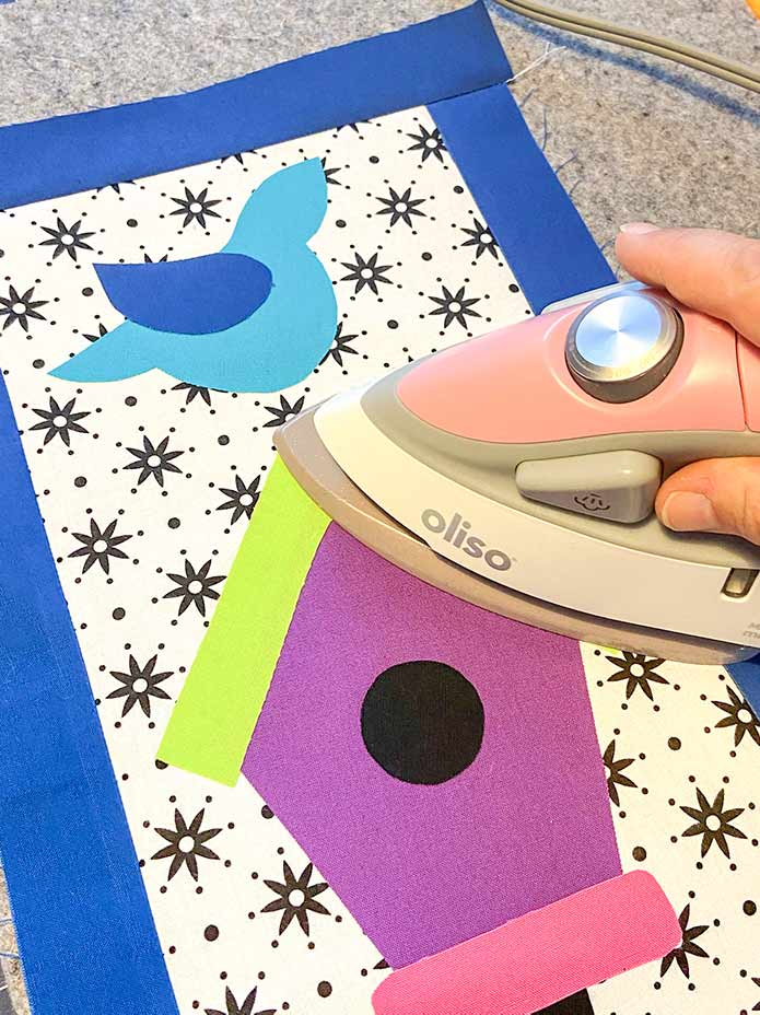 "Use an Oliso M2Pro Mini Project Iron easily fuse the applique shapes to the background fabric. Mary Ellen's Best Press, HeatnBond Lite Iron-On Adhesive Sheets, Olfa 5"" Stainless Steel Serrated Edge Scissors, Heirloom Non-Stick Teflon Applique Mat, Oliso M2Pro Mini Project Iron."