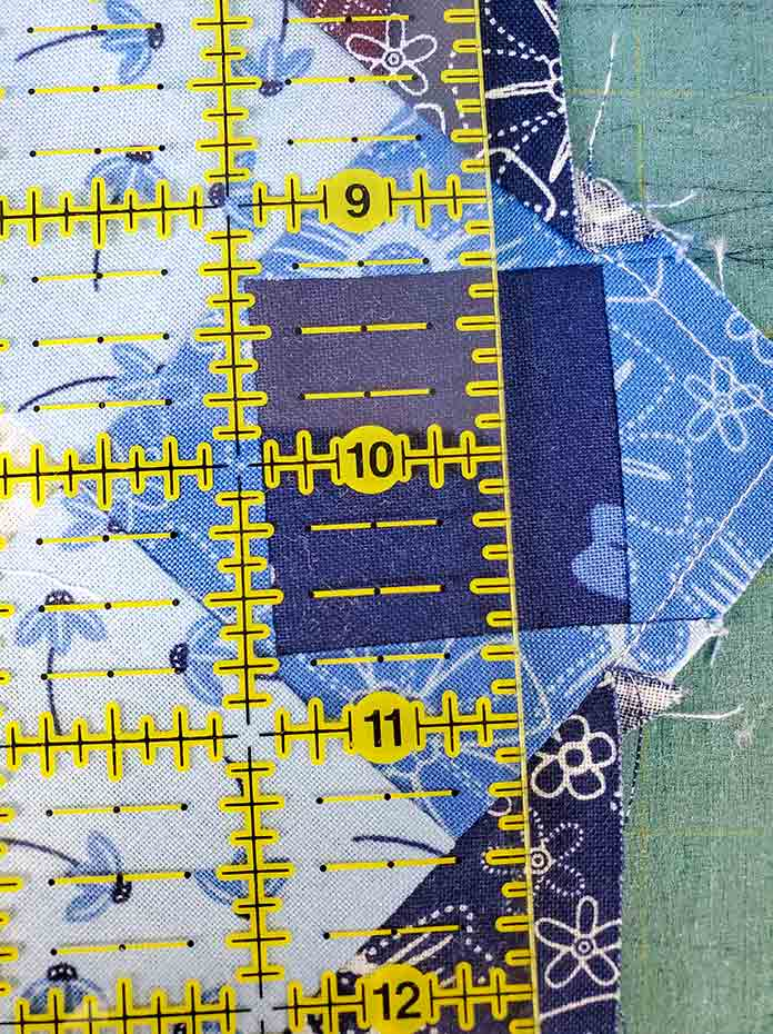 Lining up the ruler on the cornerstone to trim the edge of the blue and white quilt. Spectrum QAL2020 made with the Blue Stitch collection by Riley Blake Designs