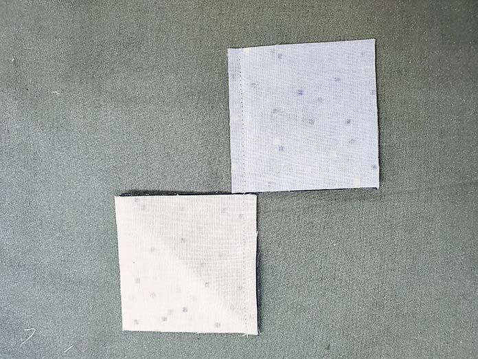 Two squares of fabric on an ironing surface