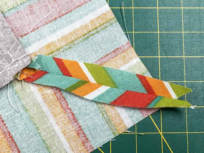 After all the mitered seams are sewn, trim away the excess border fabric and press seams open.
