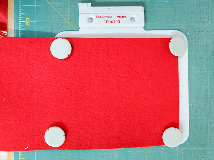 A heavy red felt has been secured in the Husqvarna Viking metal hoop with a sticky stabilizer and four magnets.