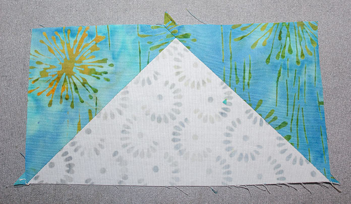 Cut on full line and press open the half square triangles to make two flying geese.
