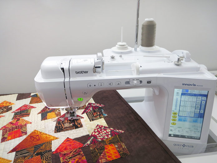"""Quilt with raw edge applique houses sitting on the bed of a sewing machine. Brother Innov-ís BQ3050 sewing and quilting machine, Mary Ellen's Best Press, Brother SA185 ¼"""" Piecing Foot with Guide, Brother SA125 ¼"""" Quilting Foot, Olfa square ruler, MuVit digital dual feed foot"""