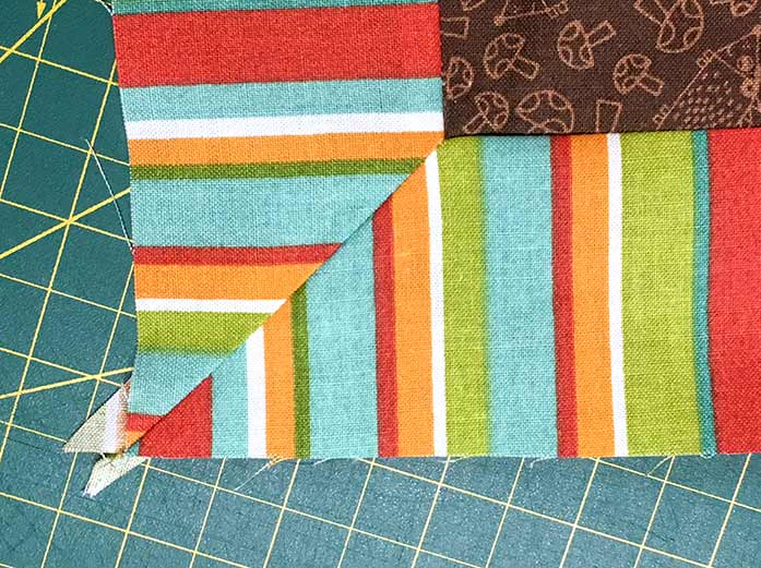 The mitered corner of the striped border on the lap quilt made with the Twisted Square ruler by Sew Easy.
