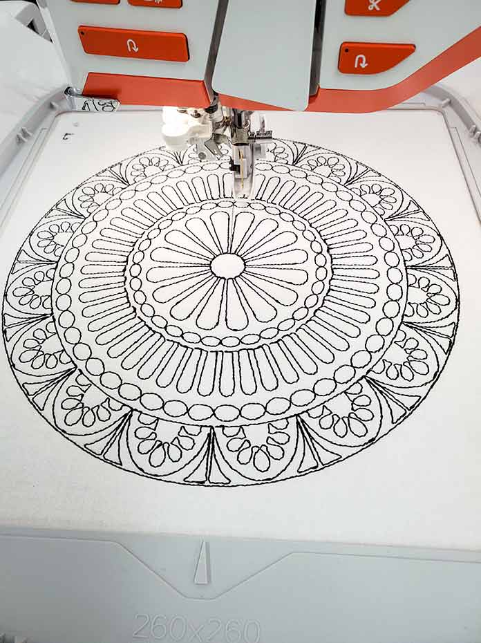 The first color of the embroidery design is almost complete with black thread on white fabric