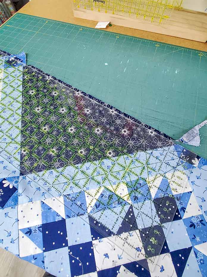 Use a long ruler to stretch between the cornerstone reference points on the blue and white quilt top. Spectrum QAL2020 made with the Blue Stitch collection by Riley Blake Designs