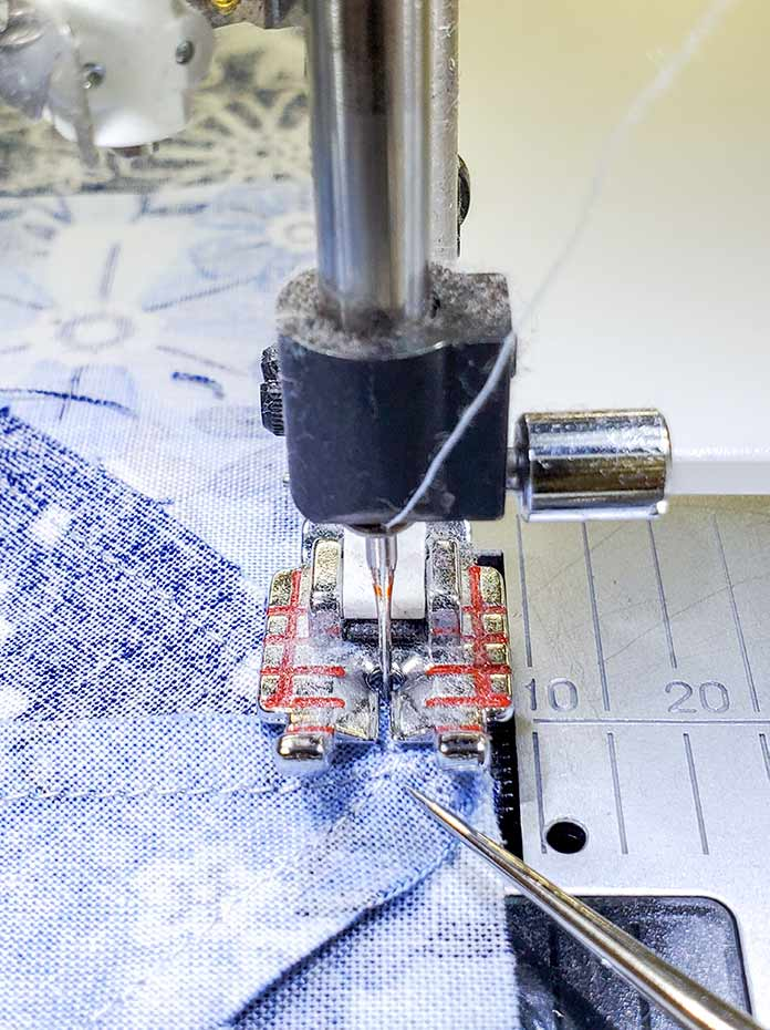 Using a quilter's awl or a stiletto to keep the seam allowance from shifting as you sew the seam; Spectrum QAL2020, Blue Stitch Fabric Collection Block 1