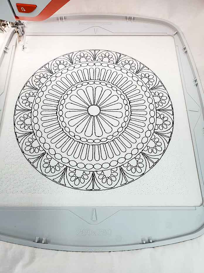 The finished outline of the machine embroidered mandala using black and white thread on white fabric; HV Designer EPIC 2