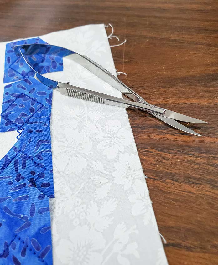 A pair of metal snips sitting on white and blue fabric