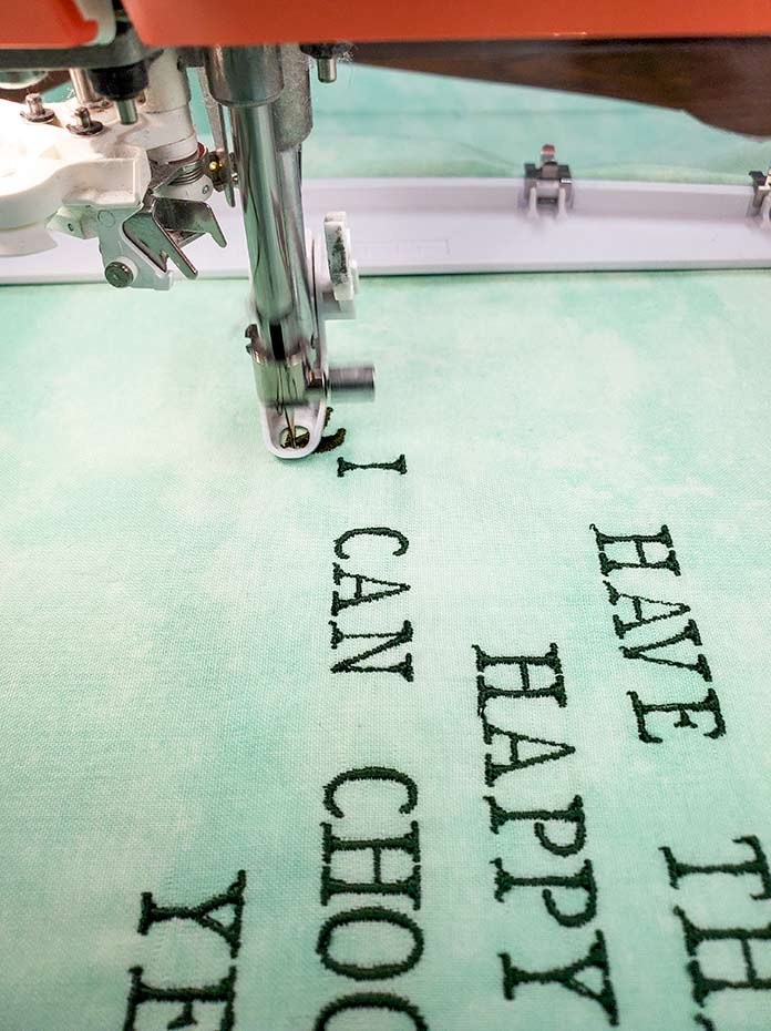 Lettering on green fabric Using 40wt thread for the lettering