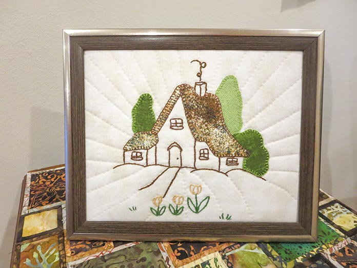 Finished embroidered and appliqued house design, Brother ScanNCut SDX225, Brother scanning mat, Brother fabric mat, Brother blue erasable marking pen, Heat n Bond Feather Lite, Brother color pen set