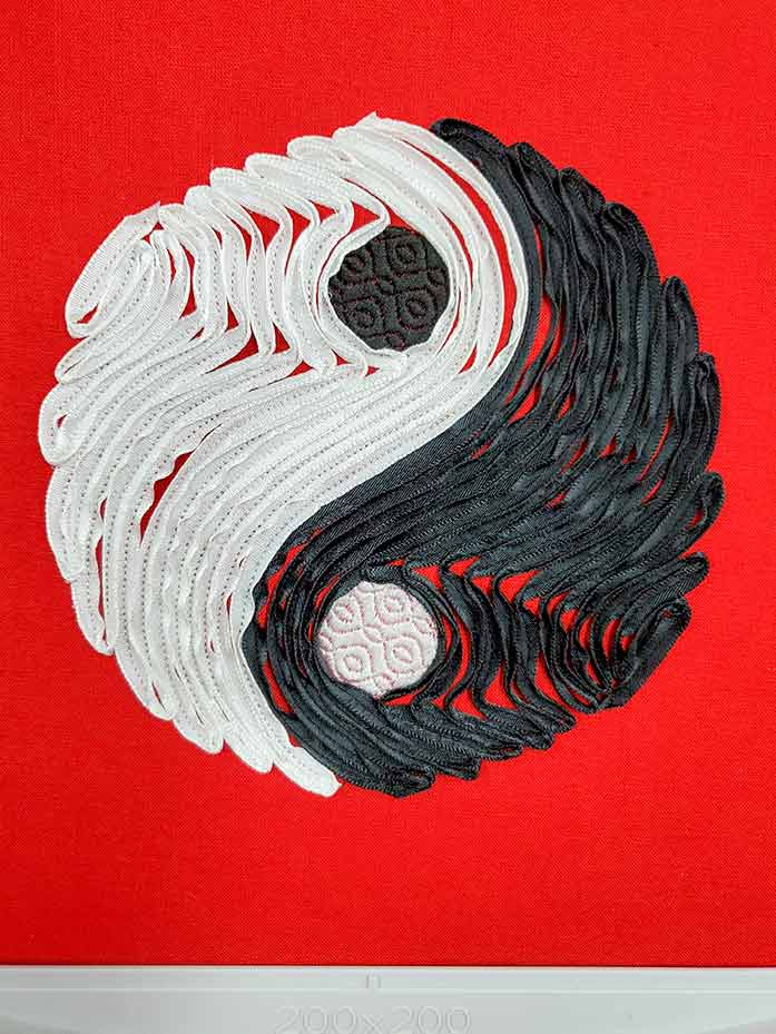 The Yin Yang design in black and white on red fabric with the ribbon tails cut away.