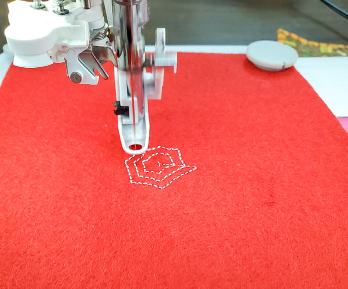 Stitching out the spider web on heavy red felt using the Husqvarna Viking DESIGNER EPIC 2