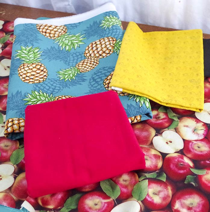The apple fabric is spread out underneath the solid red for the bottom of the bag and worm print yellow fabric for the straps and pockets. The pineapple printed fabric is on top of the very realistic apple print fabric. The apples in the fabric show the leaves, as well as some of the apples cut in half so you can see the seeds.